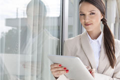 Portrait of confident businesswoman using digital tablet by glass door Stock Images