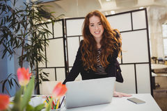 Portrait of confident businesswoman using laptop at meeting room at creative office Stock Photography