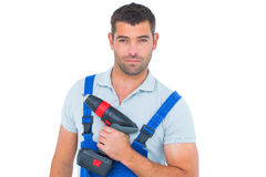Portrait of confident carpenter holding power drill. Portrait of confident male carpenter holding power drill on white background Royalty Free Stock Photography