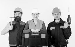 Portrait of confident carpenters carrying toolbox and tools. Against white background. Men and woman in hard hats ready to work Royalty Free Stock Photo