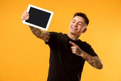 Portrait of a confident casual man showing blank screen of laptop. Portrait of a confident casual boy showing blank screen of laptop isolated over gold stock photos