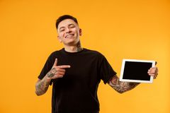 Portrait of a confident casual man showing blank screen of laptop. Portrait of a confident casual boy showing blank screen of laptop isolated over gold royalty free stock image