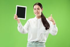 Portrait of a confident casual girl showing blank screen of laptop isolated over green background.  stock photo