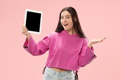 Portrait of a confident casual girl showing blank screen of laptop isolated over pink background.  royalty free stock photo