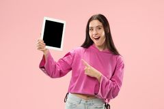 Portrait of a confident casual girl showing blank screen of laptop isolated over pink background.  stock photography