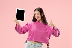 Portrait of a confident casual girl showing blank screen of laptop isolated over pink background.  royalty free stock image