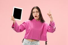 Portrait of a confident casual girl showing blank screen of laptop isolated over pink background.  stock image