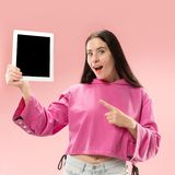 Portrait of a confident casual girl showing blank screen of laptop over pink background.  stock photography