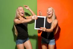 Portrait of a confident casual girls showing blank screen of laptop over colorful background. Portrait of a confident casual girls showing blank screen of laptop stock photo