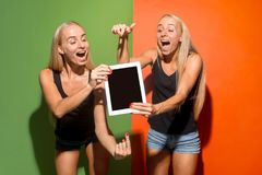 Portrait of a confident casual girls showing blank screen of laptop over colorful background. Portrait of a confident casual girls showing blank screen of laptop royalty free stock image