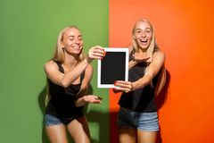 Portrait of a confident casual girls showing blank screen of laptop over colorful background. Portrait of a confident casual girls showing blank screen of laptop stock image