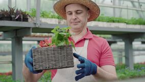 Portrait of confident Caucasian biologist examining flowers in box and smiling. Mid-adult man in straw hat checking