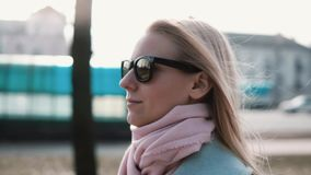 Portrait of confident Caucasian blonde girl 20s. Slow motion calm smiling young lady walking in stylish sunglasses. Portrait of confident Caucasian blonde girl stock video