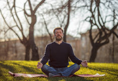 Portrait of confident caucasian man. Mature man sitting on yoga mat in comfortable asana relaxing outdoor Royalty Free Stock Image