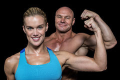 Portrait of confident cheerful man and woman flexing muscles Stock Images