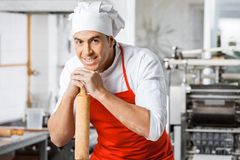 Portrait Of Confident Chef Leaning On Rolling Pin Stock Images