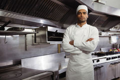 Portrait of confident chef standing with arms crossed in commercial kitchen. At restaurant stock photography
