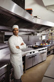 Portrait of confident chef standing with arms crossed in commercial kitchen. At restaurant royalty free stock photo