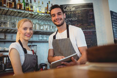 Portrait of confident colleagues with digital tablet. Standing at cafe Royalty Free Stock Images