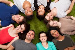 Portrait of confident college students lying on grass stock image