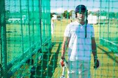 Portrait of confident cricket player wearing helmet Stock Photos
