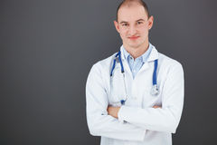 Portrait of confident doctor on gray background. Portrait of confident doctor with crossed hands on gray background looking at the camera Stock Photos