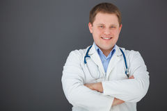Portrait of confident doctor on gray background. Portrait of happy doctor with crossed hands on gray background looking at the camera Royalty Free Stock Photo