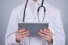 Portrait Of Confident Doctor Holding Digital Tablet Stock Photo