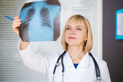 Portrait of confident doctor looking at xray. Stock Photos