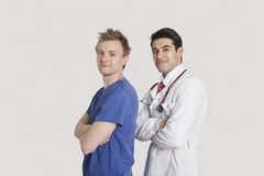 Portrait of a confident doctor and male nurse standing with arms crossed over gray background Royalty Free Stock Photos