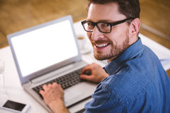 Portrait of confident executive looking over shoulder at creative office. Portrait of confident young male executive looking over shoulder at creative office Royalty Free Stock Image