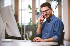 Portrait of confident executive talking on cellphone at office Royalty Free Stock Image