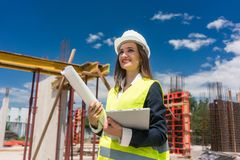 Portrait of a confident female architect or engineer with can-do attitude. Smiling while holding a rolled blueprint and a tablet on the construction site stock photo