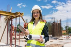 Portrait of a confident female architect or engineer with can-do attitude. Smiling while holding a rolled blueprint and a tablet on the construction site royalty free stock images