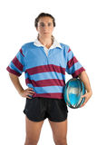 Portrait of confident female athlete with hand on hip holding rugby ball. Against white background royalty free stock photography