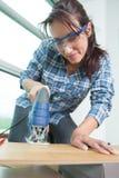 Portrait confident female carpenter using bandsaw in workshop Stock Photo