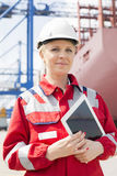 Portrait of confident female engineer holding tablet computer in shipping yard Royalty Free Stock Images