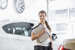 Portrait of confident female mechanic with clipboard in car workshop Stock Photography