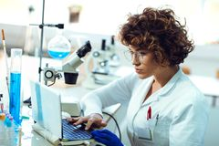 Portrait of confident female scientist working on laptop Stock Images