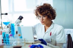 Female scientist working on laptop in chem Royalty Free Stock Photography