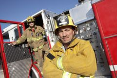 Portrait Of A Confident Firefighter. With coworker in the background Stock Images