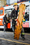 Portrait Of Confident Firefighter Holding Wooden Royalty Free Stock Image