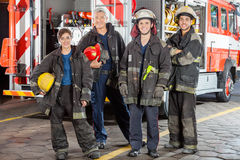 Portrait Of Confident Firefighters Standing Against Truck Stock Image
