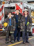 Portrait Of Confident Firefighters Standing. Full length portrait of confident firefighters standing against truck at fire station Royalty Free Stock Images