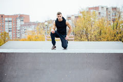 Portrait of a confident fitness guy. Man poses on skate ramp, against the background the city. Stock Image