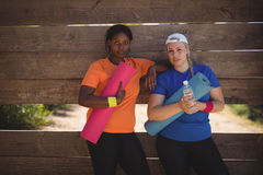 Portrait of confident friends relaxing after workout during obstacle course Royalty Free Stock Photography