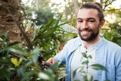 Portrait of confident gardener using hedge clippers at garden Royalty Free Stock Photo