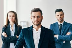 Portrait of confident handsome businessman in office with his team on background royalty free stock photography
