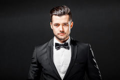 Portrait of confident handsome man in black suit with bowtie. Posing in dark studio background royalty free stock photography