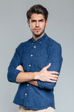 Portrait of a confident handsome man standing with arms folded Stock Images